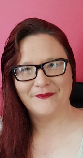 photo shows Karen Pollock, wearing glasses and with long brown hair smiling at the camera against a pink background
