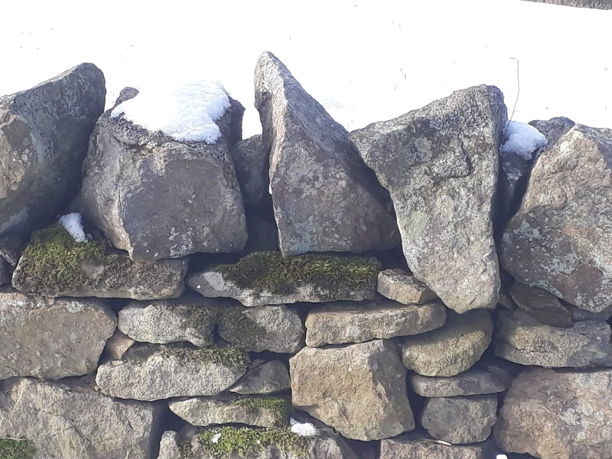 image shows a dry stone wall with snow on it