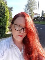 A photograph of me, outside, with my hair loose, wearing black glasses and a white shirt